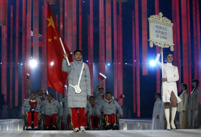 China's flag-bearer Tian Ye (C), leads his country's contingent during the opening ceremony of the 2014 Paralympic Winter Games in Sochi, March 7, 2014. REUTERS/Alexander Demianchuk (RUSSIA - Tags: OLYMPICS SPORT)