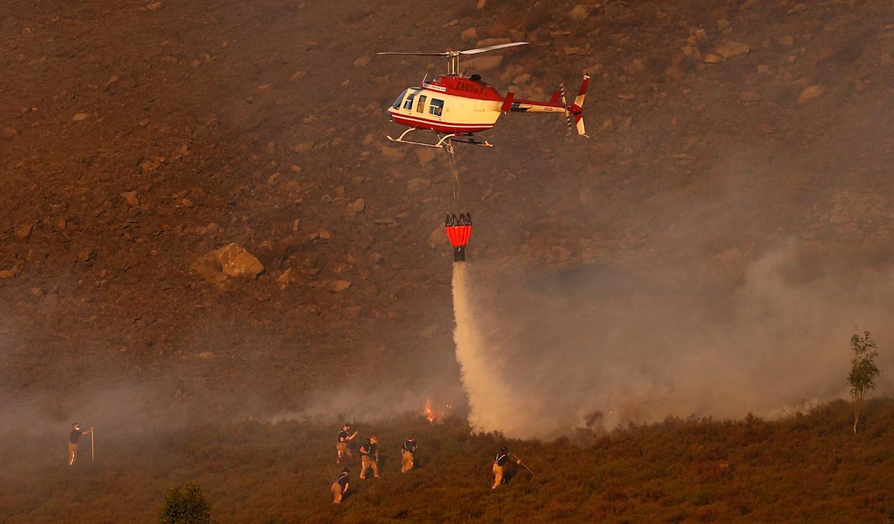 <p>A helicopter is seen dropping water onto the flames (Reuters/Phil Noble) </p>