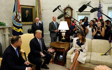 U.S. President Donald Trump speaks next to first lady Melania Trump during a meeting with Poland's President Andrzej Duda (L) in the Oval Office of the White House in Washington, U.S., September 18, 2018. REUTERS/Kevin Lamarque