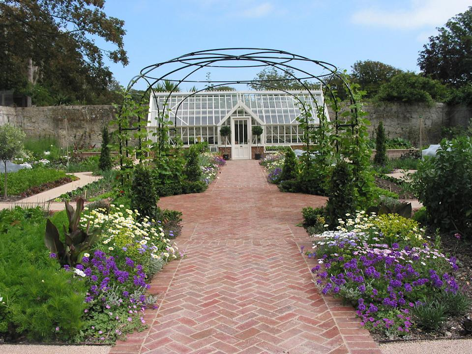 traditional handmade pavers used for a path leading to a large greenhouse