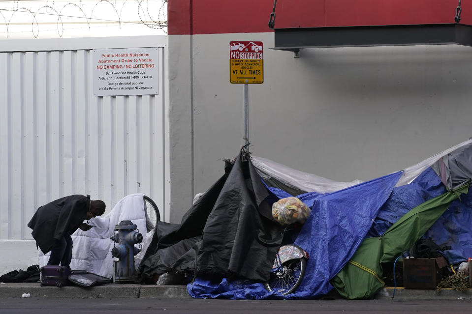 A man stands near tents set up on a sidewalk in San Francisco, Saturday, Nov. 21, 2020. Some counties in California are pushing ahead with plans to wind down a program that's housed homeless people in hotel rooms amid the pandemic, despite an emergency cash infusion from the state aimed at preventing those same residents from returning to the streets in cold, rainy weather as the virus surges. (AP Photo/Jeff Chiu)