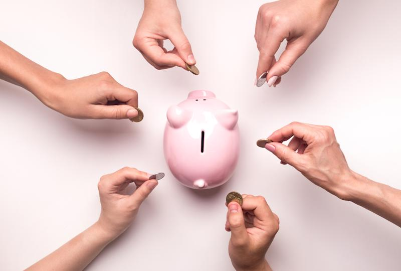 Togetherness concept. People hands throwing coins in piggy bank for crowdfunding, white background