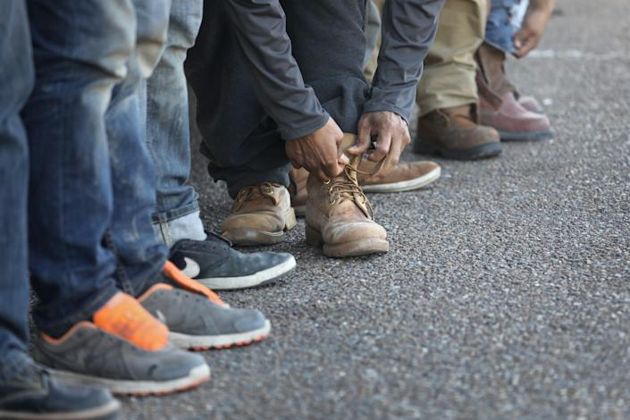An immigrant ties his shoes after receiving his laces back from the U.S. Border Patrol before being deported into Mexico from Hidalgo, Texas, on March 14, 2017.