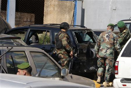Lebanese army soldiers stand near a booby-trapped car (in black) loaded with explosives in the Corniche al-Mazraa district of central Beirut February 12, 2014. REUTERS/Mohamed Azakir