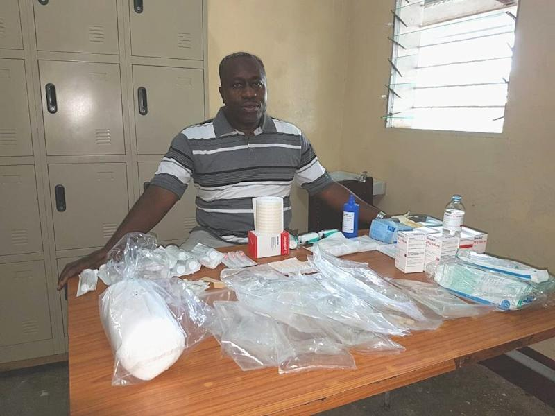 Dr. Wilfrid Mutombo sits with all the items needed to treat a single sleeping sickness patient. (DNDi)