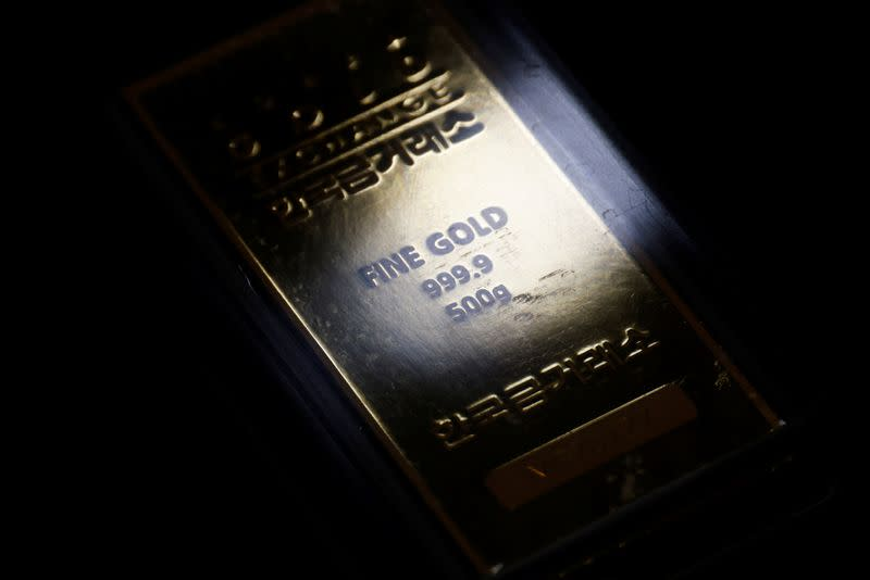 Gold dips as dollar holds onto gains; U.S.-China spat in focus
