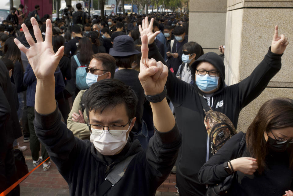 Supporters gesture as many people queue up outside a court to try to get in for a hearing in Hong Kong Monday, March 1, 2021. Pro-democracy activists detained by police on Sunday on charges of conspiracy to commit subversion under the sweeping national security law, are expected to appear in court. (AP Photo/Vincent Yu)