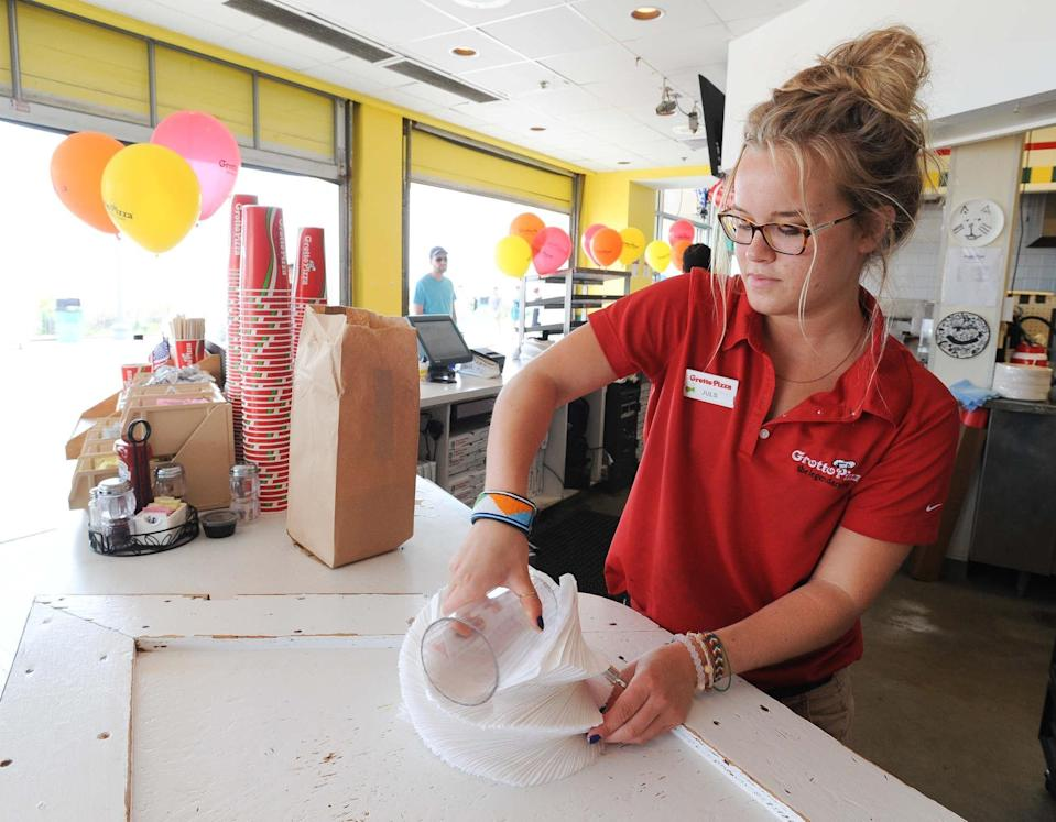 Julia Gilley, a counter sales employee at Grotto on the boardwalk in Rehoboth Beach, prepares a stack of napkins while working at Grotto for the summer in 2015, when she was attending the University of Delaware.