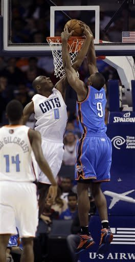 Charlotte Bobcats' Bismack Biyombo (0) tries for the block but misses as Oklahoma City Thunder's Serge Ibaka (9) dunks during the first half of an NBA basketball game in Charlotte, N.C., Friday, March 8, 2013. (AP Photo/Bob Leverone)