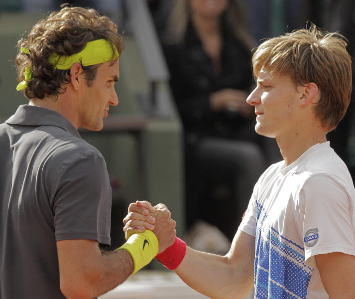 Roger Federer of Switzerland, left, shakes hands with David Goffin of Belgium, right, after winning his fourth round match at the French Open tennis tournament in Roland Garros stadium in Paris, Sunday June 3, 2012. Federer won in four sets 5-7, 7-5, 6-2, 6-4. (AP Photo/Michel Spingler)