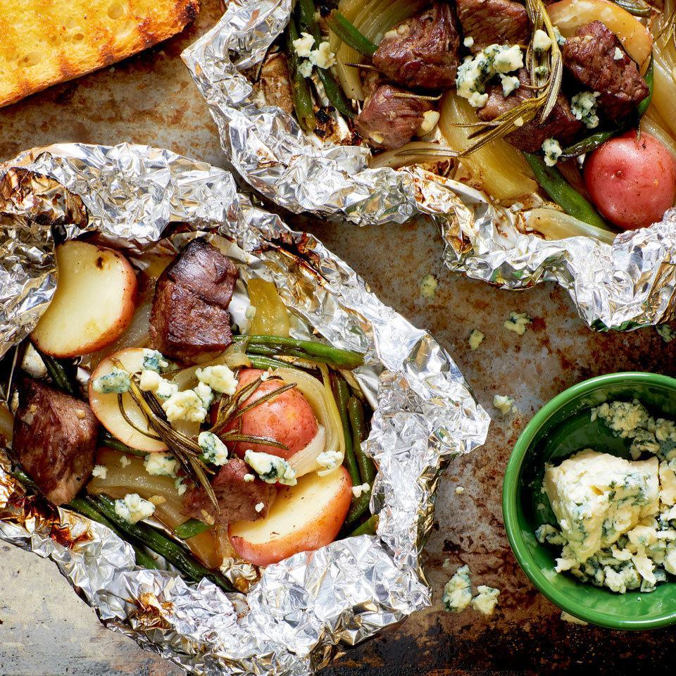 <p>Steak and potatoes are a classic combo on the grill. We have taken the concept one step further by adding green beans and rosemary, and wrapping everything in a packet to make a complete meal. A sprinkling of blue cheese just before serving is the perfect finish for this steak-house special.</p>
