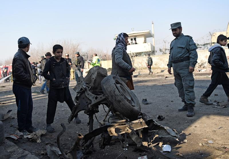 An Afghan policeman looks at the wreckage of a car that was used in a suicide car bomb near Kabul's international airport on December 28, 2015 (AFP Photo/Shah Marai )