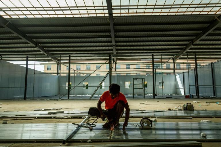 A labourer works to construct a new Covid-19 coronavirus quarantine centre in 115 Mile in Muse, near the China-Myanmar border (AFP/STR)