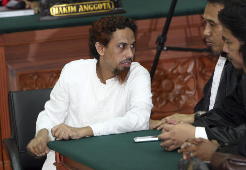 Indonesian militant Umar Patek, left, listens to his lawyer Ashludin Hatjani after being sentenced to 20 years in prison at West Jakarta district court in Jakarta, Indonesia, Thursday, June 21, 2012. Patek was convicted guilty of his role in the 2002 Bali bombings that killed 202 people. (AP Photo/Dita Alangkara)