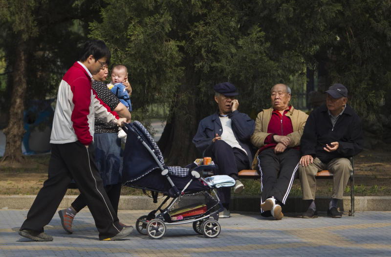"""FILE - In this April 28, 2011 file photo, elderly men rest on a bench as a family with their new born baby walk past at a park in Beijing, China. Visit your parents. That's an order. So says China, whose national legislature on Friday, Dec. 28, 2012 amended its law on the elderly to require that adult children visit their aged parents """"often"""" - or risk being sued by them. (AP Photo/Alexander F. Yuan, File)"""