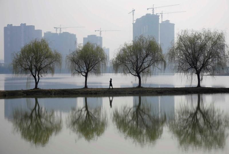 A woman walks past trees reflected on a lake in front of a construction site of a residential compound on a hazy day in Wuhan