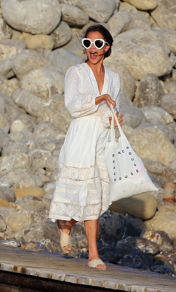 <p>Vikander wears a white Zimmermann cotton dress with matching heart-shaped sunglasses in Ibiza. (Photo: Splash) </p>