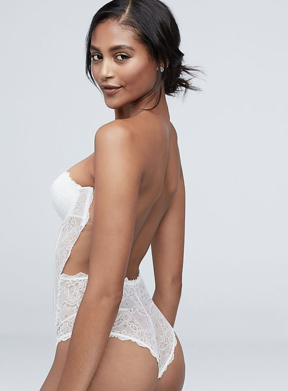 a model wearing a backless strapless lace bodysuit for underneath a wedding dress