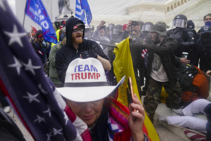 FILE - In this Jan. 6, 2021, file photo, rioters try to break through a police barrier, at the Capitol in Washington. (AP Photo/John Minchillo, File)