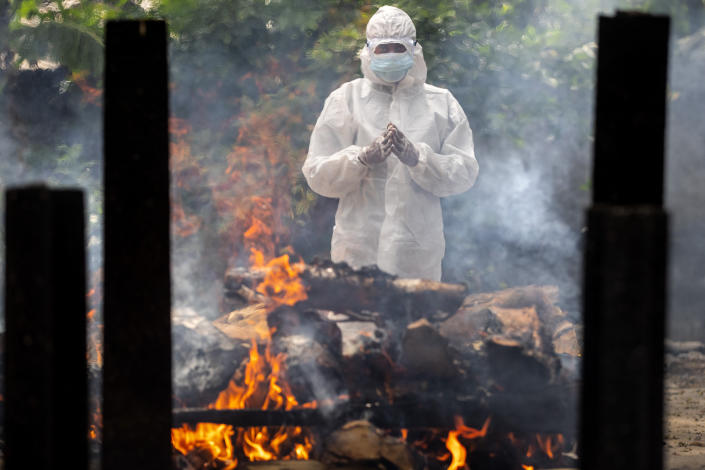 A relative in protective suit performs last rituals near the body of a person who died of COVID-19 during cremation in Gauhati, India, Monday, May 24, 2021. India crossed another grim milestone Monday of more than 300,000 people lost to the coronavirus as a devastating surge of infections appeared to be easing in big cities but was swamping the poorer countryside. (AP Photo/Anupam Nath)