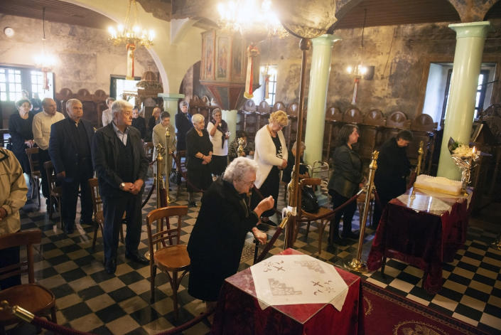 In this Sunday, May 24, 2020, photo, the faithful attend Sunday Mass at a Greek Orthodox church in the northern city of Thessaloniki, Greece. Priests at the church still use a traditional shared spoon to distribute Holy Communion. Contrary to science, the Greek Orthodox Church says it is impossible for any disease, including the coronavirus, to be transmitted through Holy Communion. (AP Photo/Giannis Papanikos)