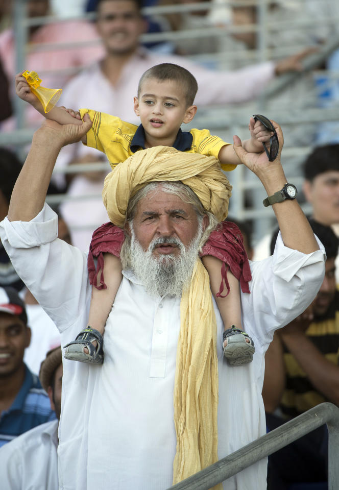 A Pakistani supporter with a child seated on his shoulders watches the match Pakistan vs South Africa on the third day of their first Test against South Africa at the Sheikh Zayed Cricket Stadium in Abu Dhabi on October 16, 2013. South Africa lost four top-order batsmen against a spirited Pakistan and they now need another 121 runs to avoid an innings defeat and concede the lead in the two-Test series. AFP PHOTO/STR        (Photo credit should read STR/AFP/Getty Images)