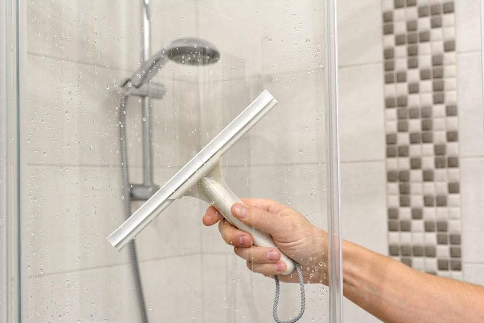 """Want to keep your bathroom cleaner without spending hours scrubbing? Then it's time to break out the squeegee. """"Keeping it stored on a hook inside the shower,"""" suggests <strong>James Scott</strong>, co-founder of <a href=""""https://dappirclean.com/"""" rel=""""nofollow noopener"""" target=""""_blank"""" data-ylk=""""slk:Dappir"""" class=""""link rapid-noclick-resp"""">Dappir</a>, a residential cleaning company. Scott explains that this is so helpful because """"the mineral content of the shower water settles on the tiles, walls, and glass over time,"""" leaving hard-to-clean spots if you don't wipe them away while they're still wet. And if you're looking to get your space spotless, check out these <a href=""""https://bestlifeonline.com/old-school-cleaning-tricks/?utm_source=yahoo-news&utm_medium=feed&utm_campaign=yahoo-feed"""" rel=""""nofollow noopener"""" target=""""_blank"""" data-ylk=""""slk:33 Mind-Blowing Old-Fashioned Cleaning Tips That Actually Work"""" class=""""link rapid-noclick-resp"""">33 Mind-Blowing Old-Fashioned Cleaning Tips That Actually Work</a>."""