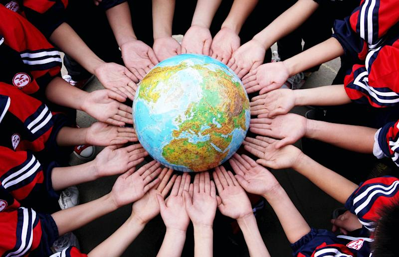 Students pose for a photo with a globe during a campaign to mark World Earth Day in a middle school in Dexing, Jiangxi province April 19, 2011. (Photo: REUTERS/China Daily)