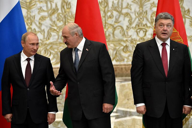 Belarus President Alexander Lukashenko (C) talks to Russia's President Vladimir Putin (L) as Ukrainian counterpart Petro Poroshenko looks away in the Belarussian capital Minsk on August 26, 2014