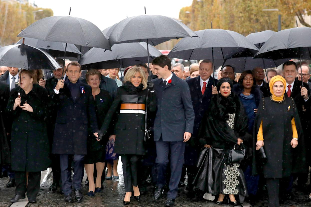 French President Emmanuel Macron's wife, Brigitte Macron (center left) listens to Canadian Prime Minister Justin Trudeau (center right) as they walk with world leaders toward the Arc de Triomphe in Paris on Sunday. (Photo: THE ASSOCIATED PRESS)