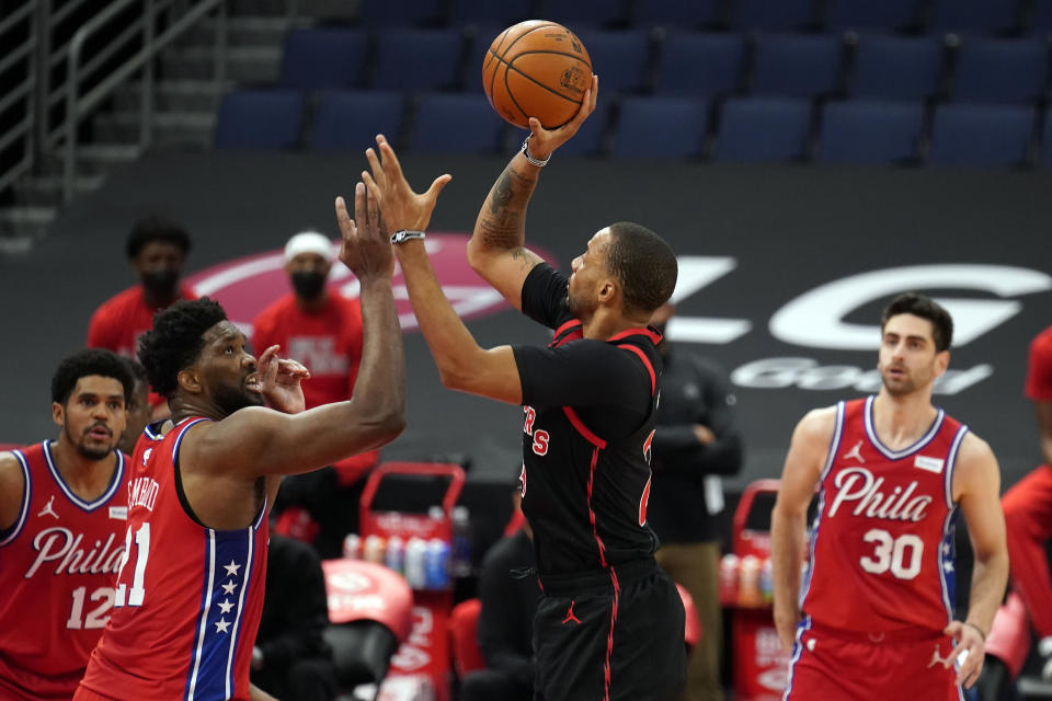Toronto Raptors guard Norman Powell (24) shoots over Philadelphia 76ers center Joel Embiid (21) during the first half of an NBA basketball game Tuesday, Feb. 23, 2021, in Tampa, Fla. (AP Photo/Chris O'Meara)