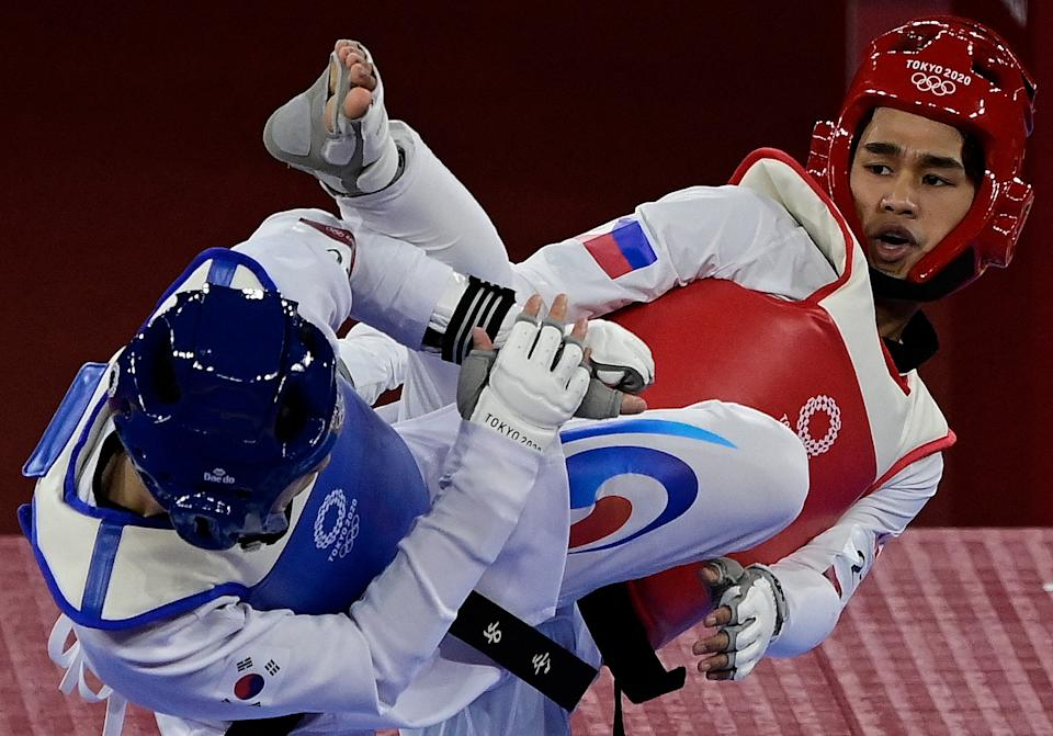 South Korea's Jang Jun (Blue) and Philippines' Kurt Bryan Barbosa (Red) compete in the taekwondo men's -58kg elimination round bout during the Tokyo 2020 Olympic Games at the Makuhari Messe Hall in Tokyo on July 24, 2021. (Photo by Javier SORIANO / AFP) (Photo by JAVIER SORIANO/AFP via Getty Images)