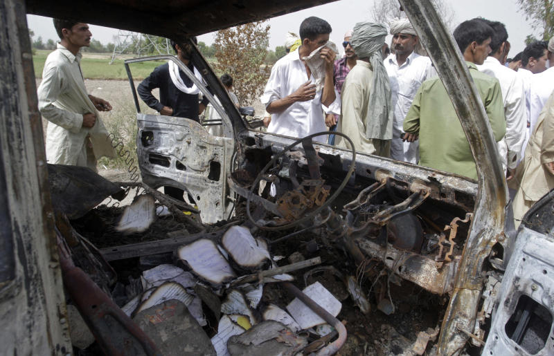 Pakistanis gather by the wreckage of a minibus, which was burnt after gas cylinder explosion, in Gujrat, Pakistan, Saturday, May 25, 2013. Police say that a teacher was among more than a dozen people burned to death in eastern Pakistan when a minibus taking children to school suddenly caught fire. (AP Photo/K.M. Chaudary)