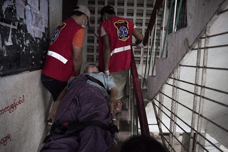 Noble Heart rescue ambulance charity service volunteers shift a patient to his home after taking him from a hospital in Yangon (AFP Photo/Nicolas Asfouri)