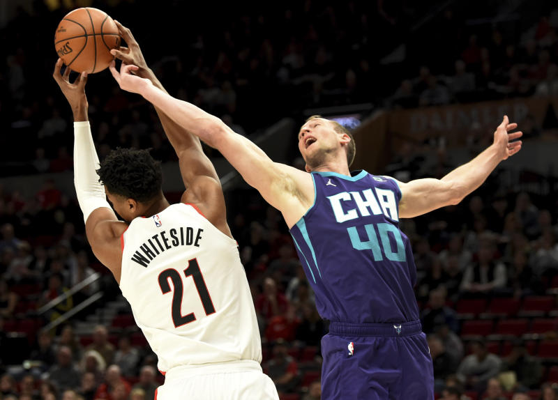 Portland Trail Blazers center Hassan Whiteside, left, grabs a rebound in front of Charlotte Hornets forward Cody Zeller, right, during the first half of an NBA basketball game in Portland, Ore., Monday, Jan. 13, 2020. (AP Photo/Steve Dykes)