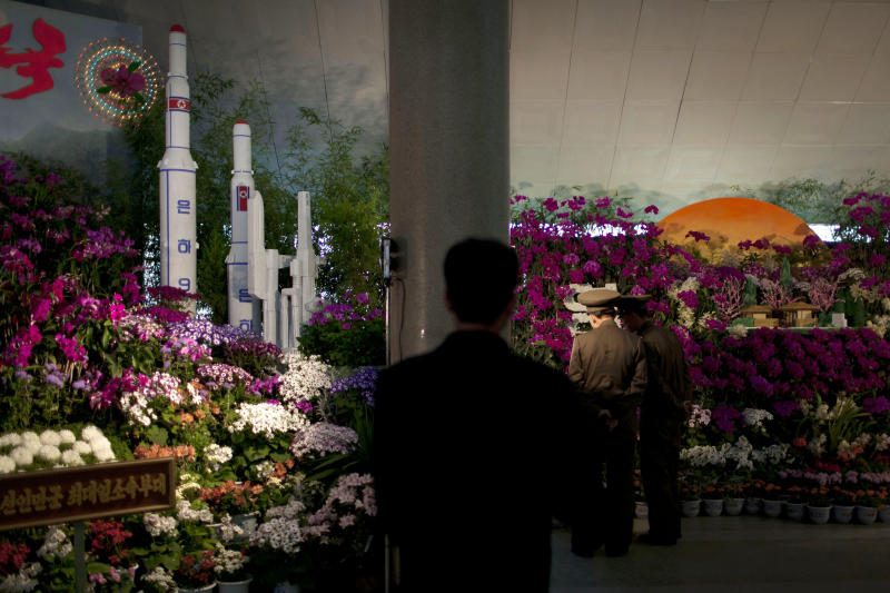 Two military officers admire displays at a flower show featuring thousands of Kimilsungia flowers, named after the late leader Kim Il Sung, while models of rockets and missiles are also exhibited in Pyongyang, North Korea, Friday, April 12, 2013. (AP Photo/Alexander F. Yuan)