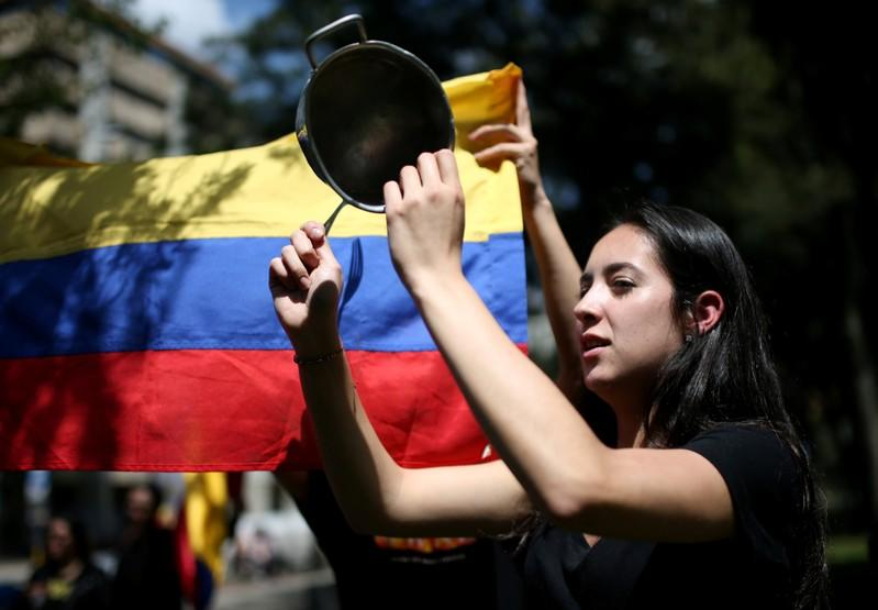A demonstrator bangs a pot during a protest in National Park as national strike continues in Bogota
