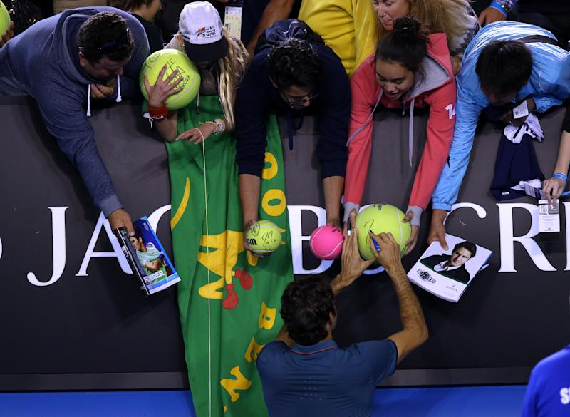 Roger Federer of Switzerland signs autographs for fans after defeating Andy Murray of Britain in their quarterfinal at the Australian Open tennis championship in Melbourne, Australia, Wednesday, Jan. 22, 2014.(AP Photo/Aaron Favila)