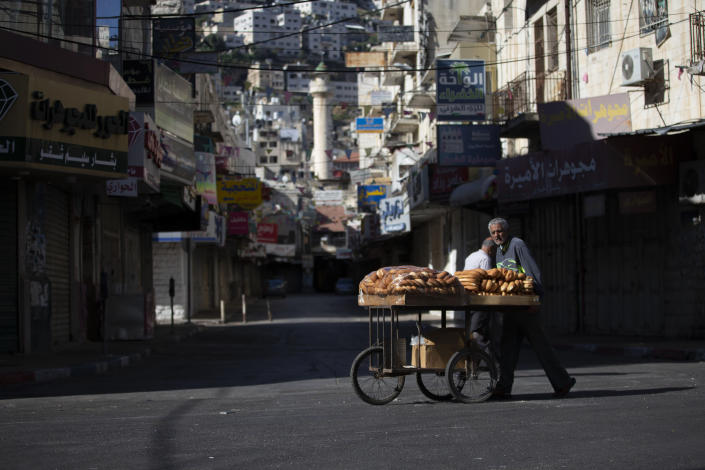 A Palestinian vendor pushes a cart loaded with bread during a general strike, in the West Bank city of Nablus, Tuesday, May 18, 2021. Palestinian leaders are calling for a general strike in Gaza, the West Bank and within Israel to protest against Israel's air strikes on Gaza and the violent confrontations between Israeli security forces and Palestinians in Jerusalem. (AP Photo/Majdi Mohammed)