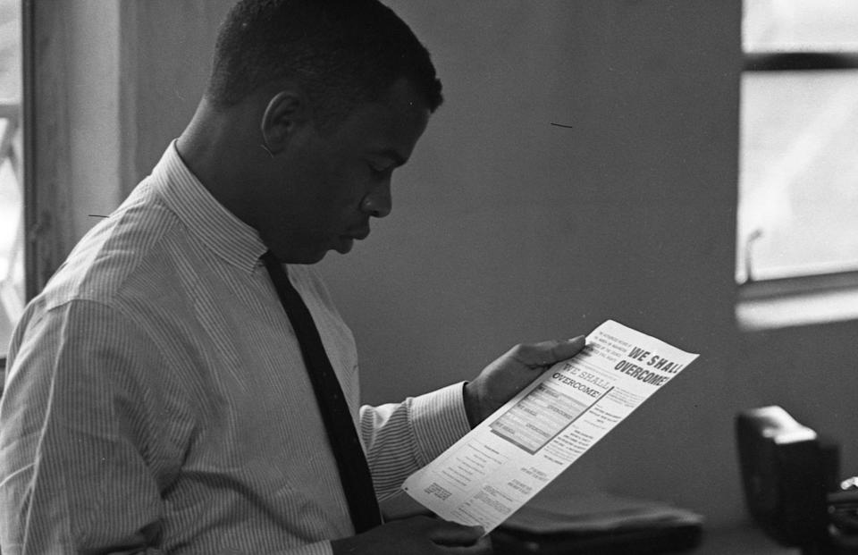 """Civil Rights activist (and future politician) John Lewis, chairman of the Student Nonviolent Coordinating Committee (SNCC), in an office, New York, 1964. He reads a document titled """"We Shall Overcome; the Authorized Record of the March on Washington Produced by the Council for United Civil Rights Leadership."""" (Photo: Robert Elfstrom/Villon Films/Getty Images)"""