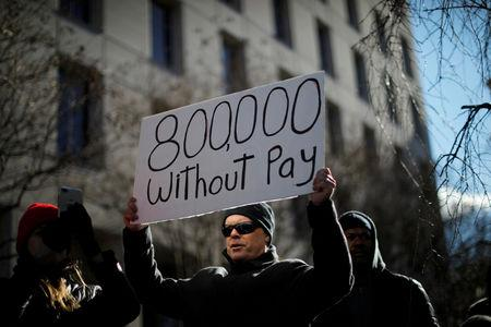 FILE PHOTO: Demonstrator holds a sign protesting the partial U.S. government shutdown