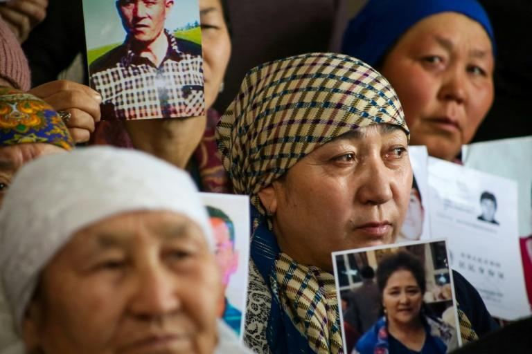 Petitioners with relatives missing or detained in Xinjiang hold up photos of their loved ones during a press event at the office of the Ata Jurt rights group in Almaty, Kazakhstan, on January 21, 2019