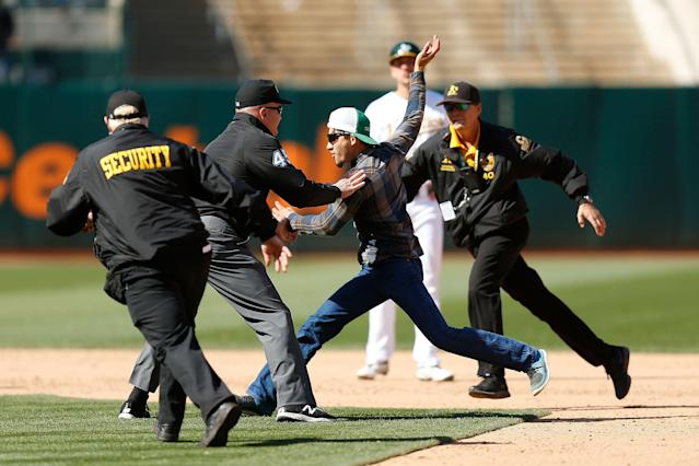 Umpire Jeff Nelson tackled a fan who ran on the field Saturday afternoon in Oakland. (Getty Images)