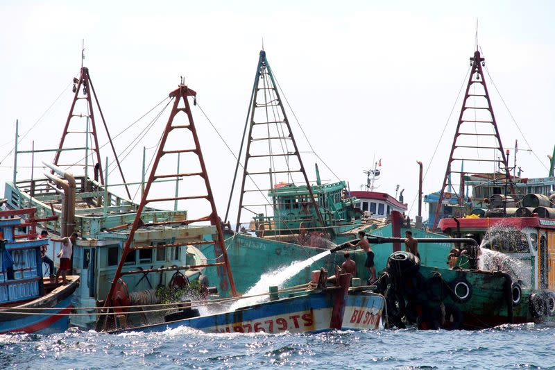 FILE PHOTO: Workers fill Vietnamese fishing boats with water to sink them after they were seized due to illegal fishing in Indonesia's waters, at Datuk island in West Kalimantan