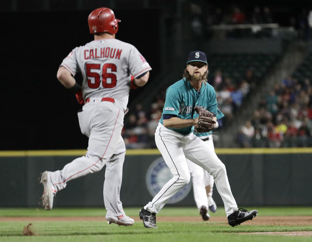 Seattle Mariners starting pitcher Mike Leake, right, prepares to put out Los Angeles Angels' Kole Calhoun, who grounded out to him during the eighth inning of a baseball game Friday, July 19, 2019, in Seattle. (AP Photo/Ted S. Warren)