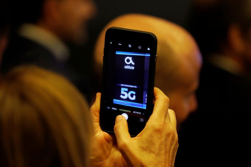 FILE PHOTO: A woman takes pictures during the first demonstration of the technology 5G in Lisbon