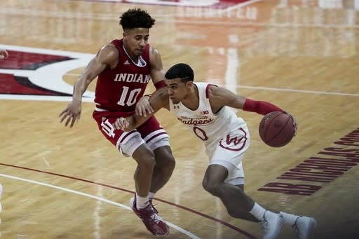 Wisconsin's D'Mitrik Trice tries to drive past Indiana's Rob Phinisee during the first half of an NCAA college basketball game Thursday, Jan. 7, 2021, in Madison, Wis. (AP Photo/Morry Gash)