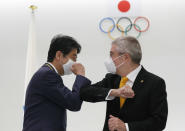 FILE - In this Nov. 16, 2020, file photo, former Japan's Prime Minister Shinzo Abe, left, and Thomas Bach, President of the International Olympic Committee (IOC), bump elbows after a ceremony to present the Olympic Order to Abe at Japan Olympic Museum in Tokyo. IOC officials say the Tokyo Olympics will open on July 23 and almost nothing now can stop the games from going forward. (Kim Kyung-hoon/Pool Photo via AP, File)