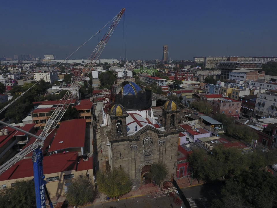 A crane lowers a steel arch into place overtop the damaged cupola, as part of a frame that will support a temporary metal roof, in the early stages of reconstruction work at Nuestra Senora de Los Angeles, or Our Lady of Angels church, three years after an earthquake collapsed nearly half of its 18th-century dome in Mexico City, Wednesday, Sept. 23, 2020. It is a titanic challenge: crumbling old stone and lime mortar walls and domes, without an ounce of cement or rebar, have to be built back with the same ancient materials. (AP Photo/Rebecca Blackwell)