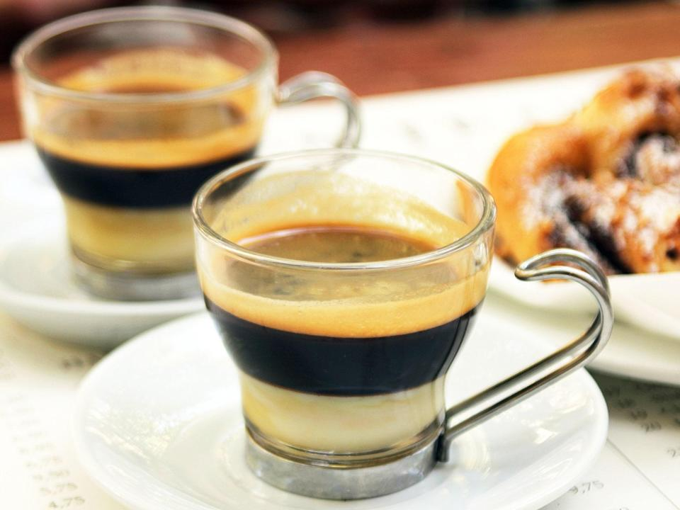 """<p>This rich, condensed milk drink originates from Valencia but resembles some beverages of Southeast Asia. It is made by pouring the coffee and milk in a way that creates three tiers of tan crema, dark coffee, and white milk. It's typically served in a clear glass, and stirred before drinking.</p> <p><strong>Try it at home:</strong> <a href=""""https://fave.co/3cgewwY"""" rel=""""nofollow noopener"""" target=""""_blank"""" data-ylk=""""slk:$15 Clear Bodum Bistro Mug at crateandbarrel.com"""" class=""""link rapid-noclick-resp"""">$15 Clear Bodum Bistro Mug at crateandbarrel.com</a></p>"""